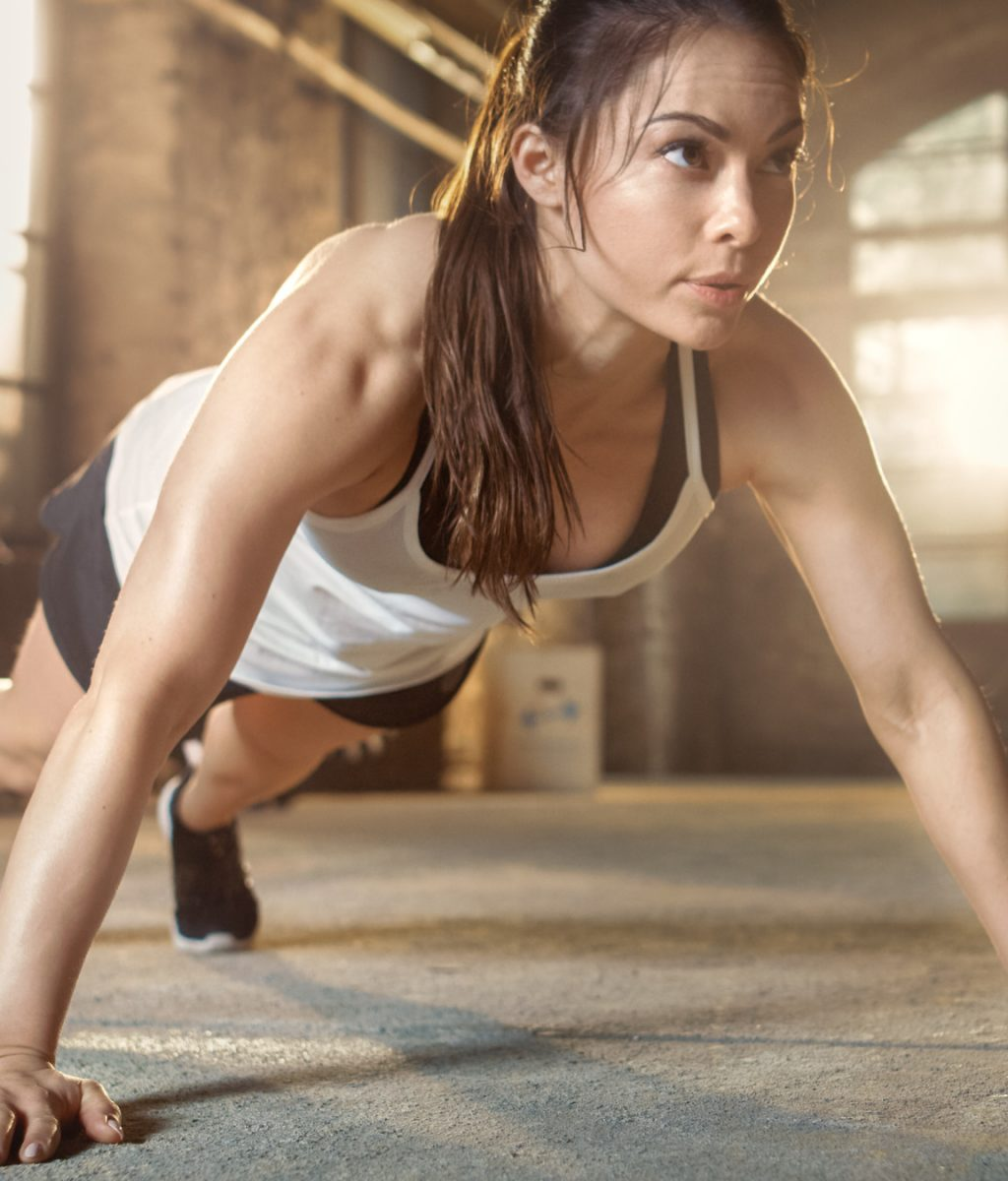 Athletic Beautiful Woman Does Push-ups as Part of Her Cross Fitness, Bodybuilding Gym Training Routine.